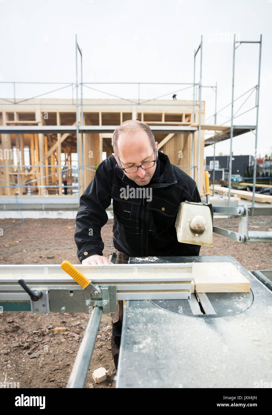 Carpenter Using Table Saw To Cut Wood At Site - Stock Image