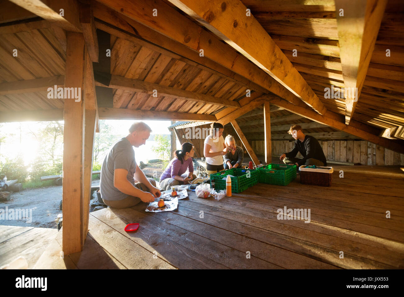 Business People Preparing Food In Shed At Forest - Stock Image