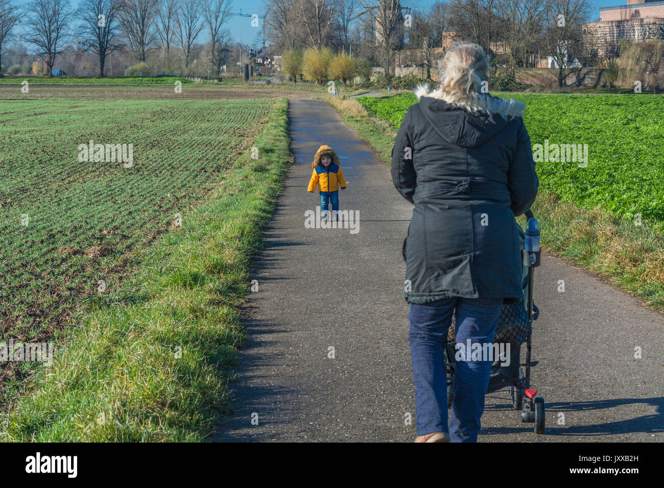 Grandmother with grandson while walking and pushes a baby carriage. - Stock Image