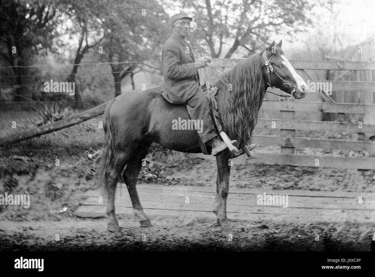 Full length sitting portrait of mature African man riding horse (Old Uncle 'Billy' on BWB's pony), wearing dark suit, glasses and hat, sitting outdoors in front of wooden fence, neutral expression, 1920. - Stock Image