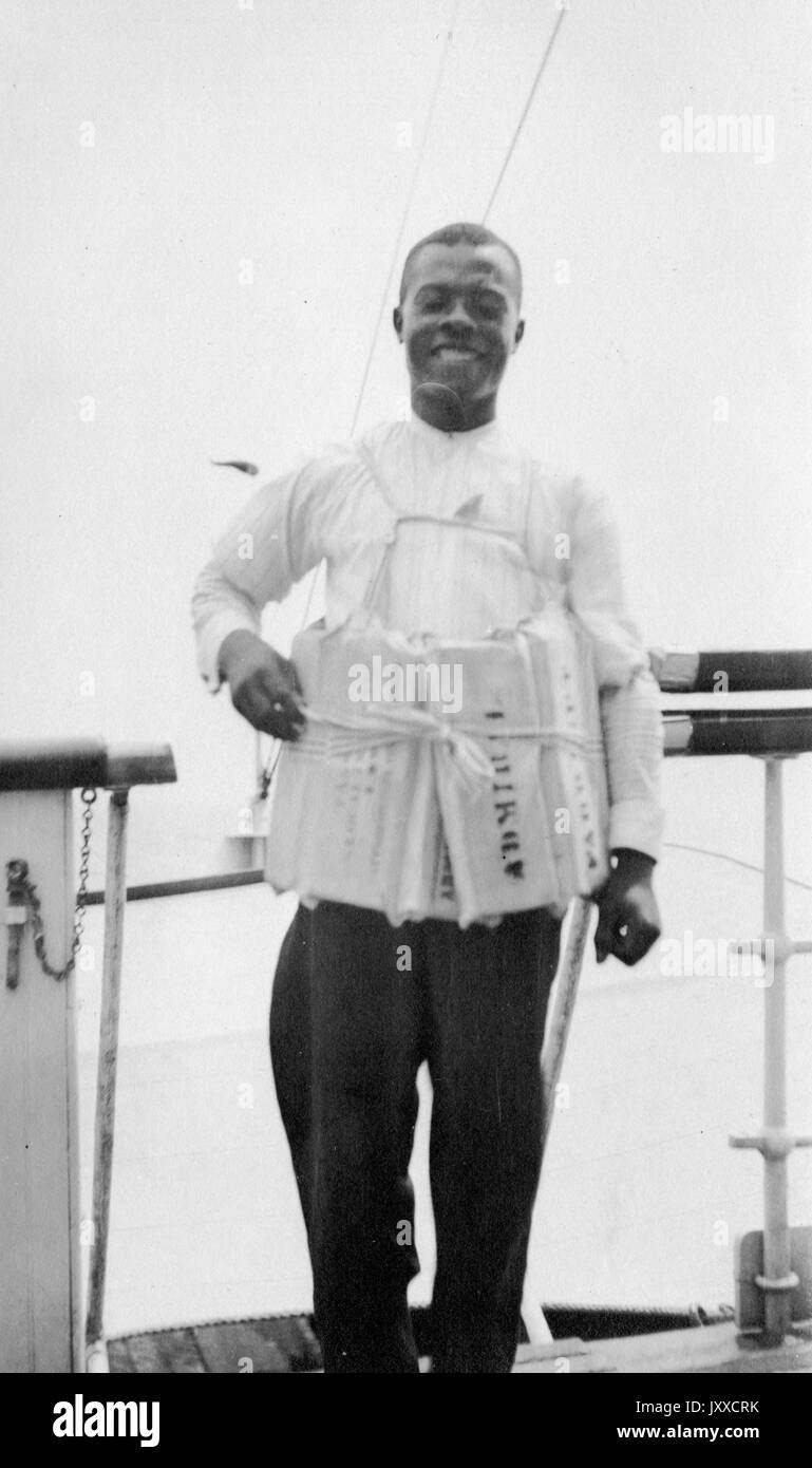 Three-quarter portrait of African American man, standing up, with parchments tied around his body, with a smiling facial expression, wearing a white shirt and dark pants, 1920. - Stock Image