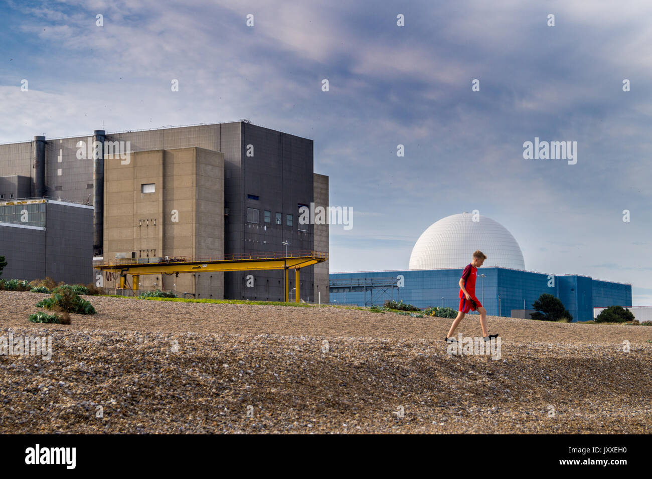 A young boy walking on the beach in front of  of Sizewell A Magnox and Sizewell B PWR nuclear reactors, Sizewell Beach, Suffolk, England - Stock Image