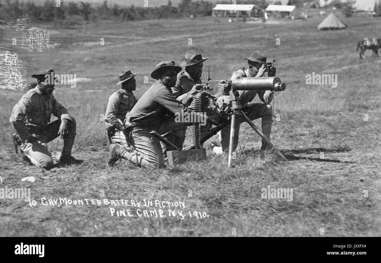 Landscape shot, African American soldiers crouched in grass around mounted battery in action, 1910. - Stock Image