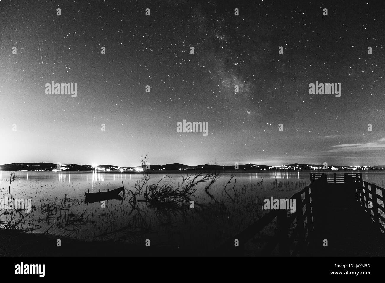 Beautiful view of night sky with milky way in the center, over a lake with pier, trees and a little boat - Stock Image