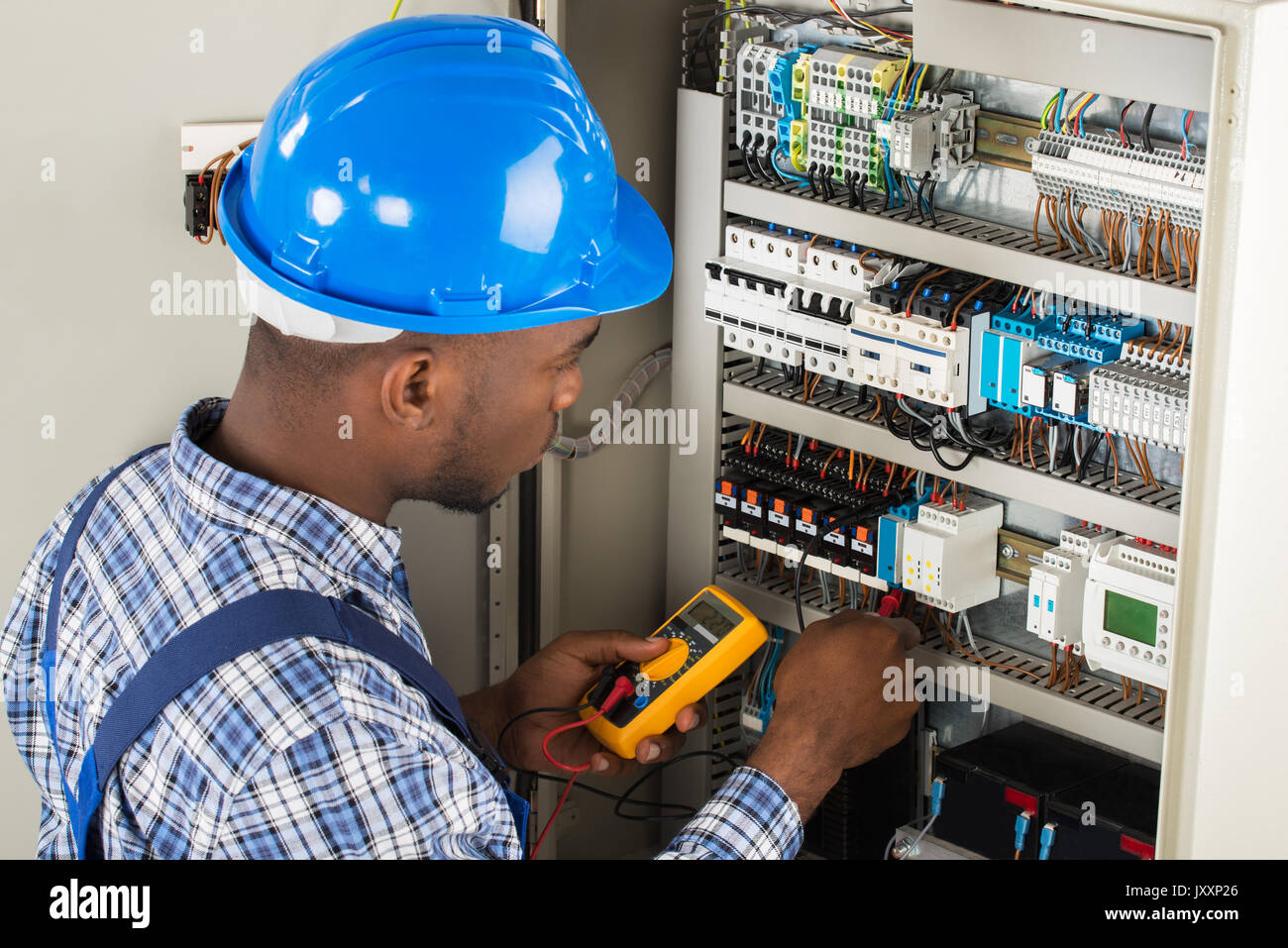 Young African Male Technician Examining Fusebox With Multimeter Probe - Stock Image