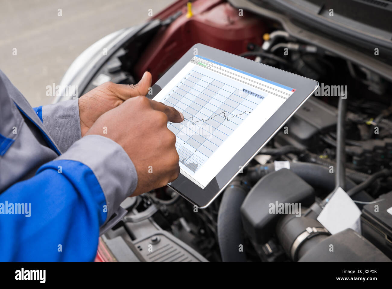 Close-up Of Mechanic With Digital Tablet Showing Graph While Examining Car - Stock Image