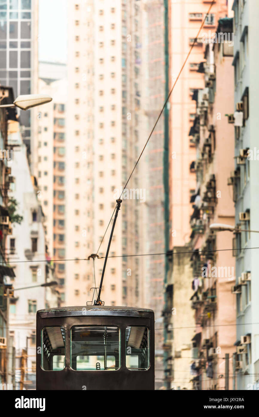 View along tall houses at street in Hong Kong and upper deck of tramway with pantograph and catenary wire - Stock Image
