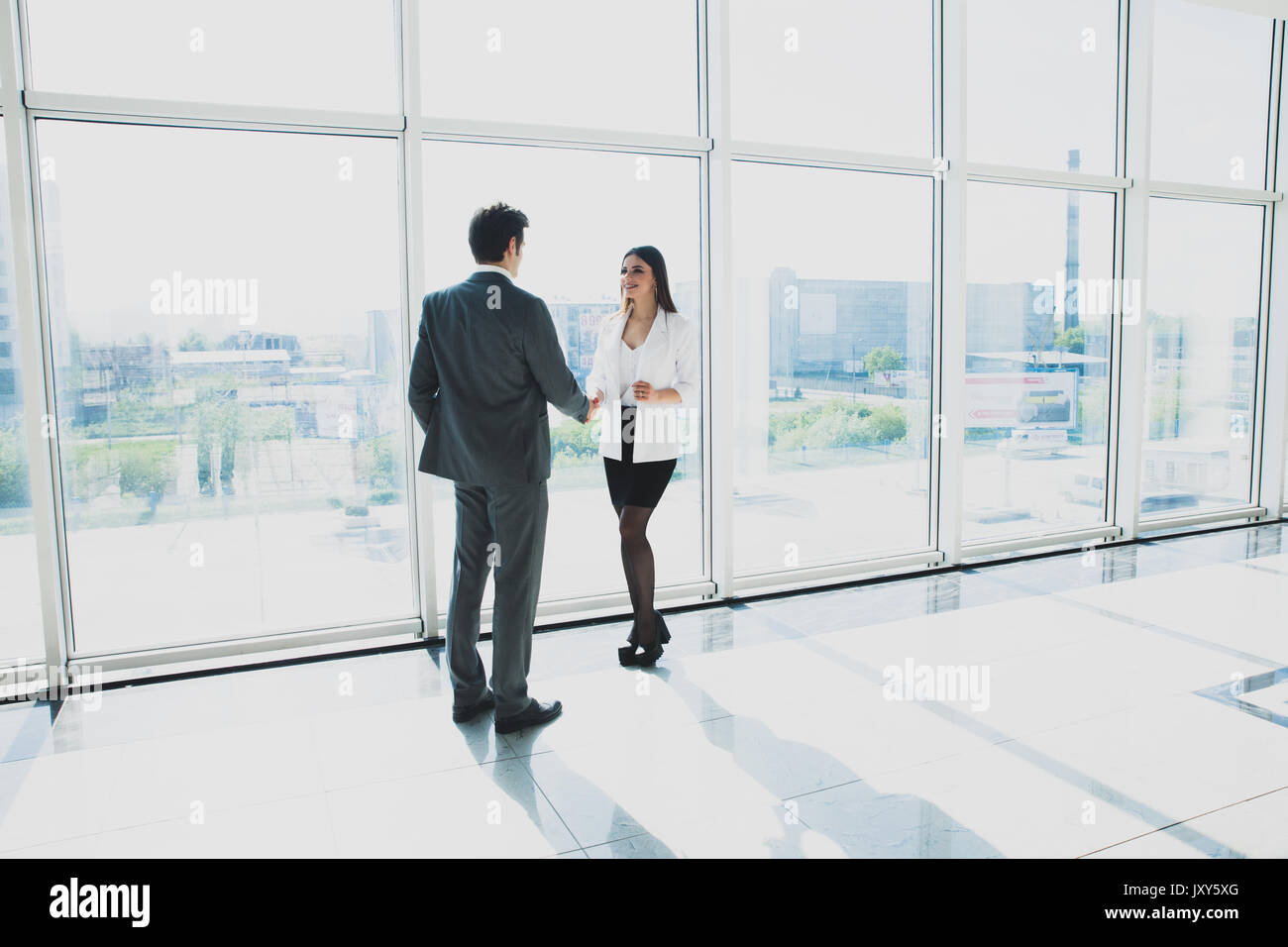 View from below of two young businessmen are standing in modern office with panoramic windows. - Stock Image