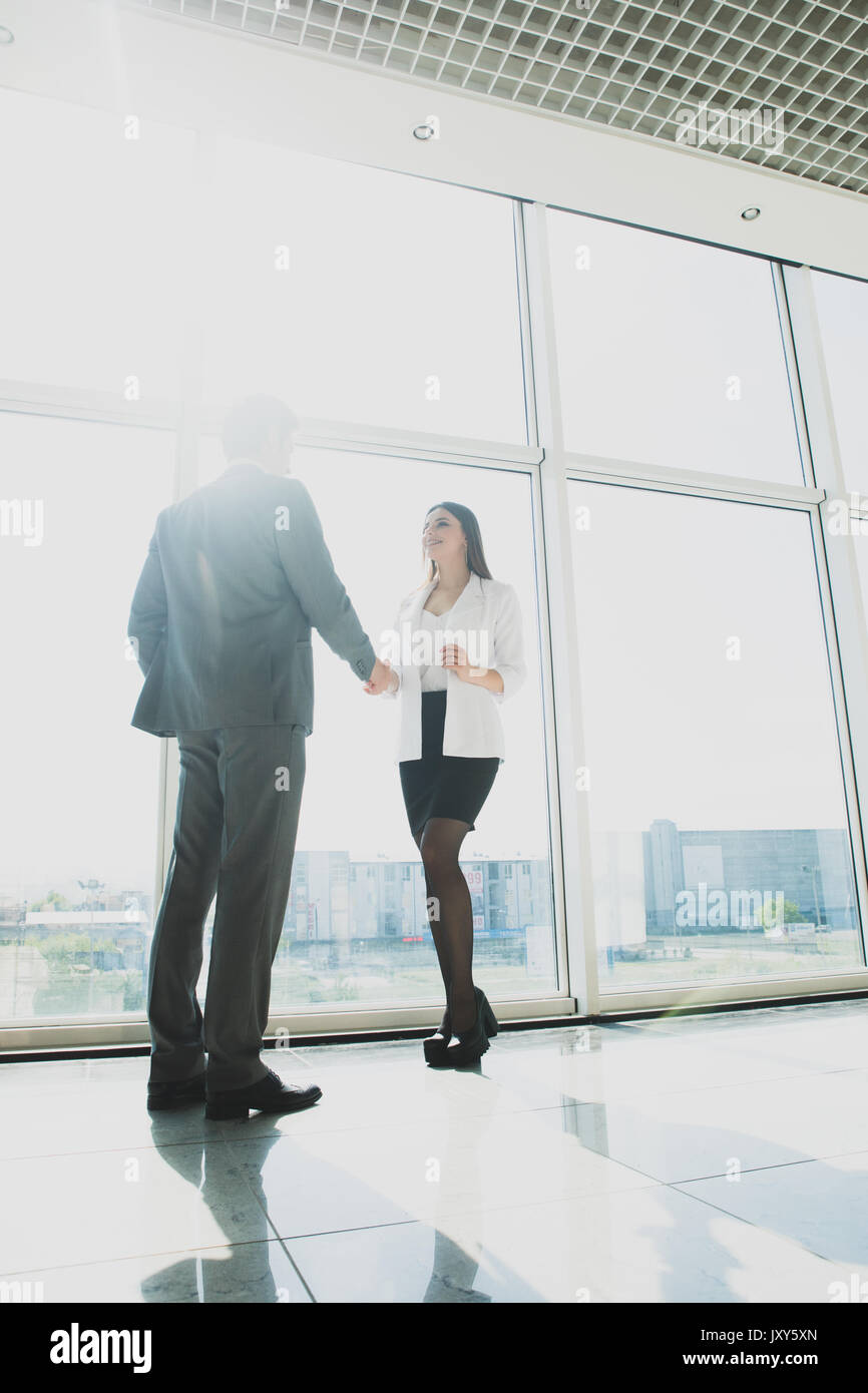 business, teamwork, cooperation and people concept - business people shaking hands over panoramic office windows - Stock Image