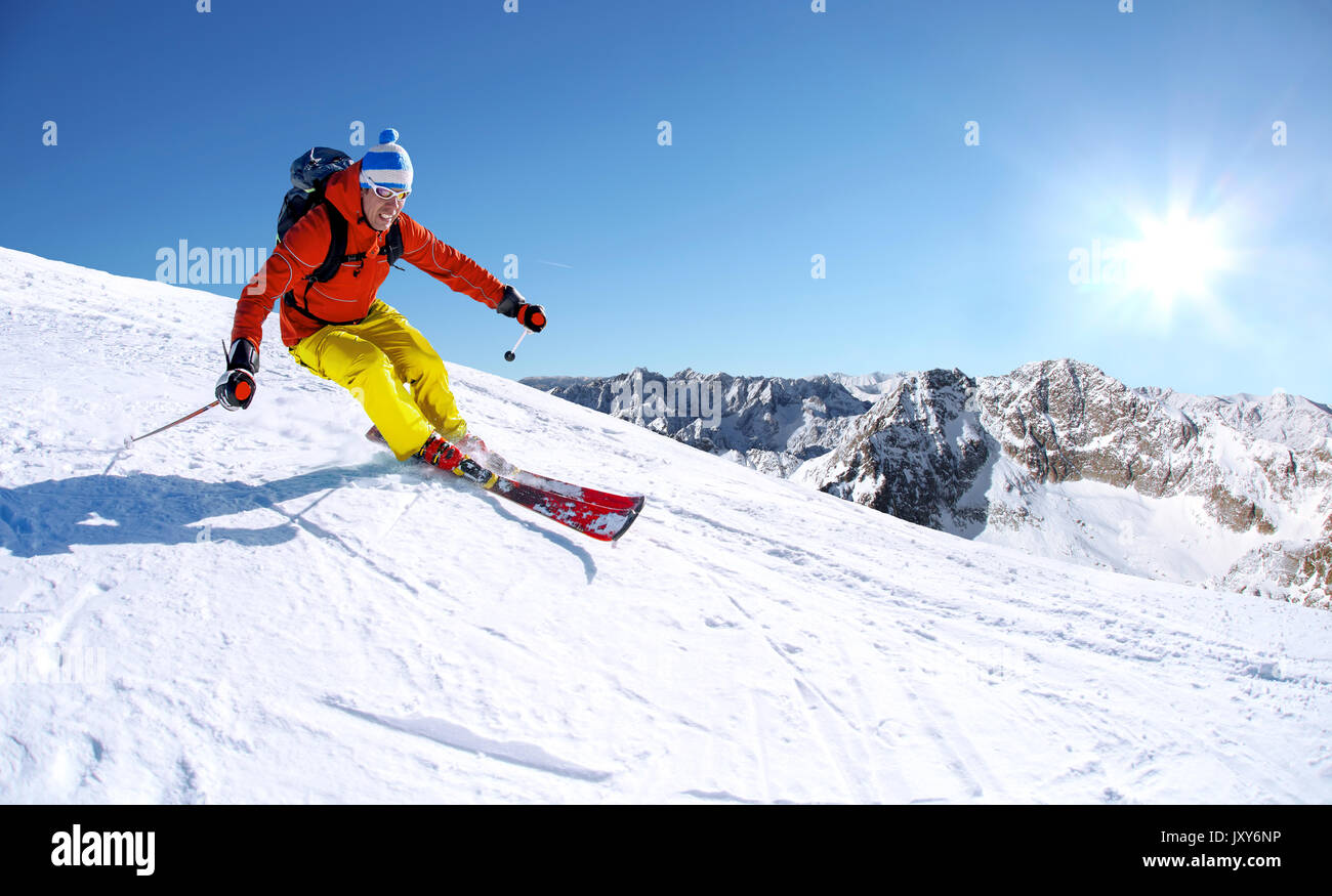 Skier skiing downhill in high mountains against blue sky - Stock Image