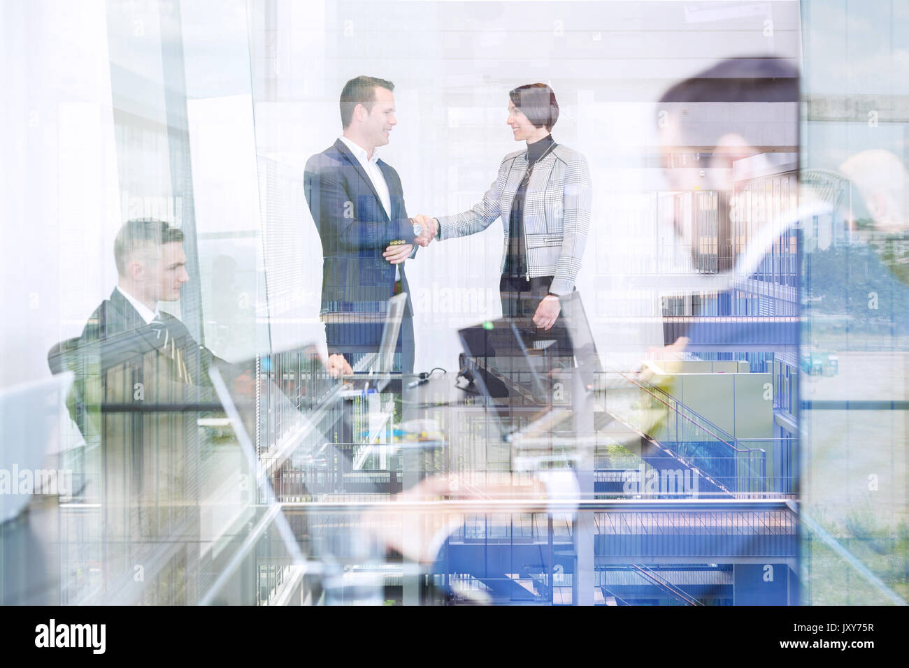 Business people shaking hands in moder corporate office. - Stock Image