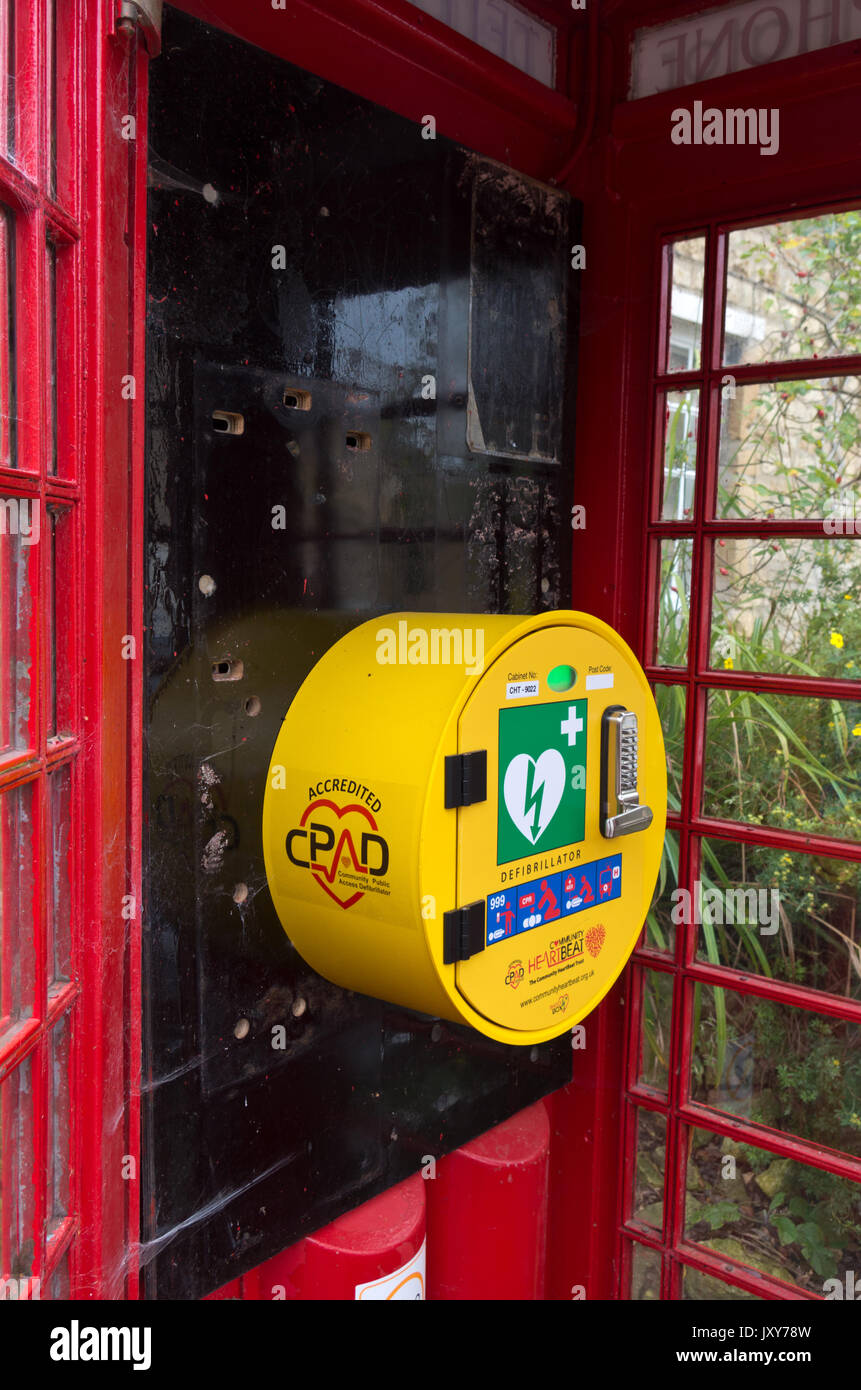 Old red telephone kiosk in the village of Geddington, now used as a defibrillator unit, part of the BT Adopt A Kiosk scheme. - Stock Image