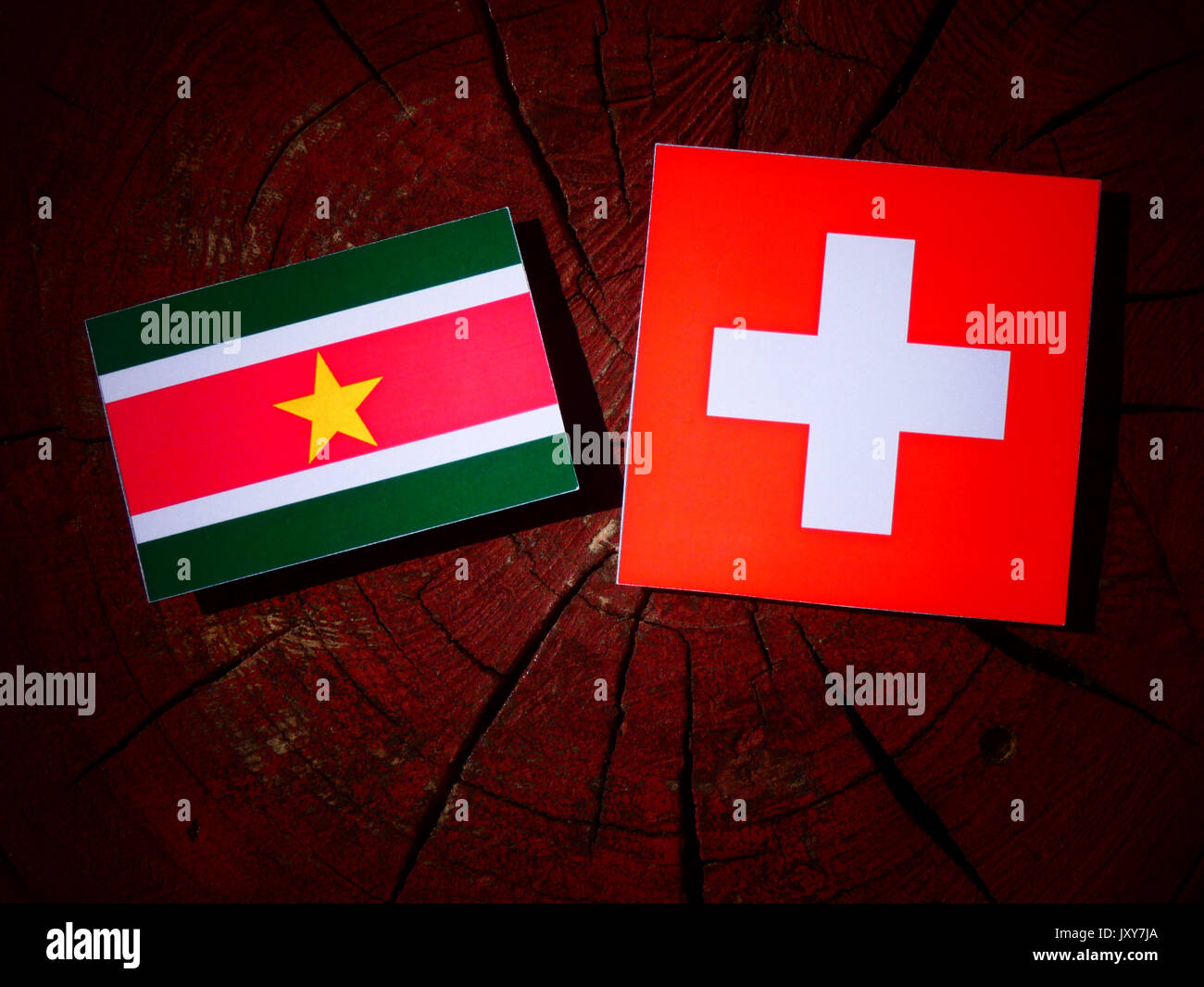 Suriname flag with Swiss flag on a tree stump isolated - Stock Image