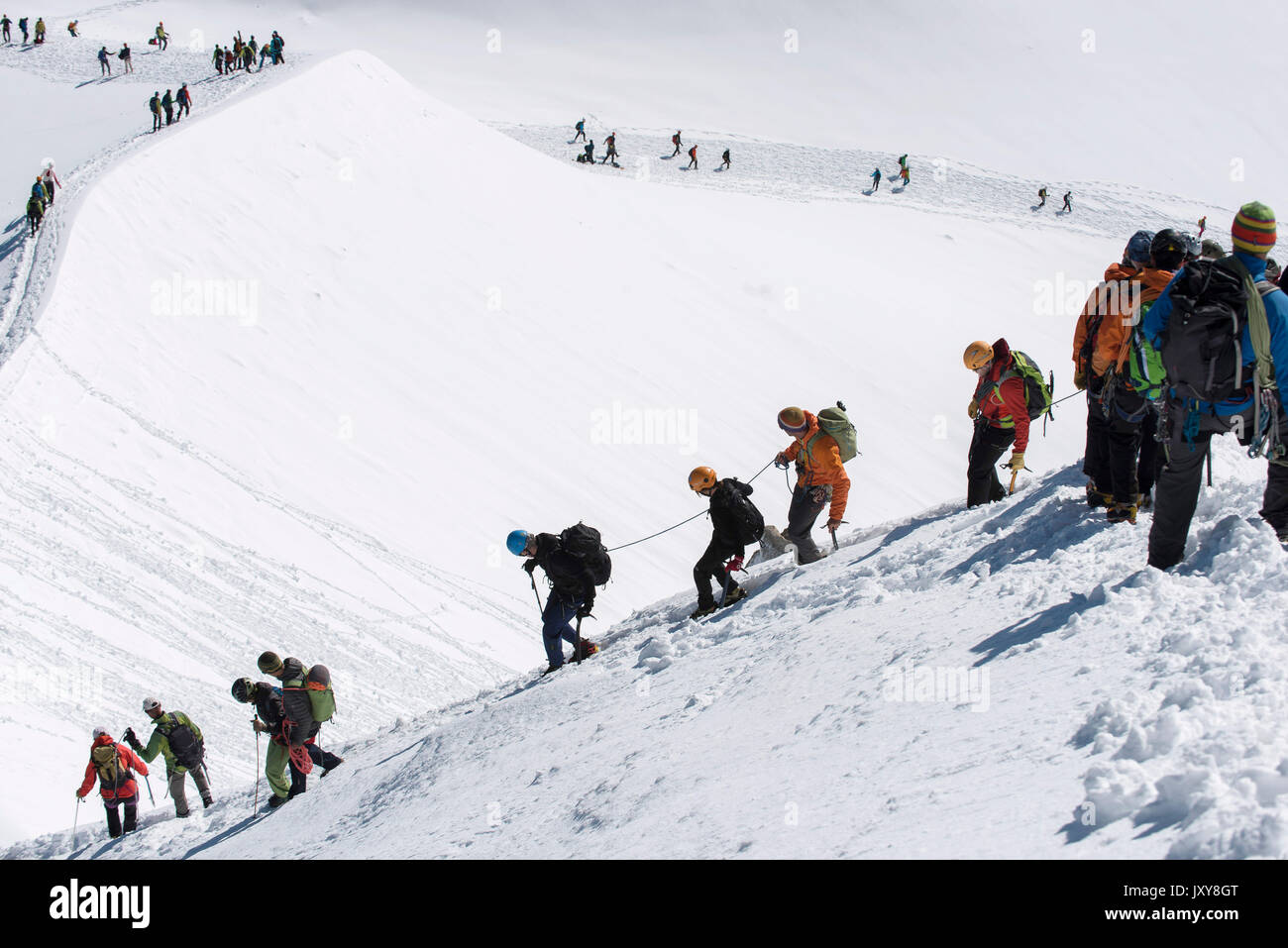 Climbers roped together on their way to the Aiguille du Midi mountain - Stock Image