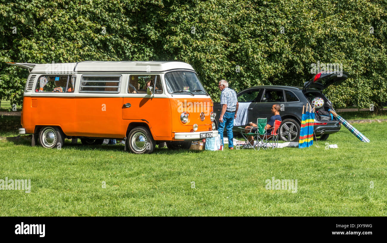 People next to a classic vintage orange Volkswagen VW campervan, enjoying the sunshine on the Burghley House estate, near Stamford, England, UK. - Stock Image