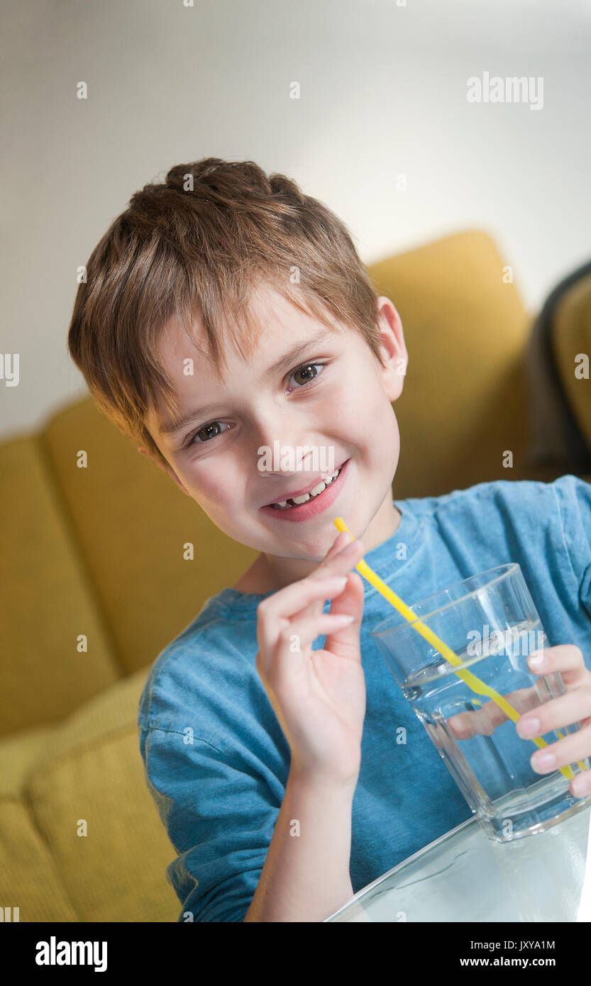 7-year old boy drinking water through a straw - Stock Image