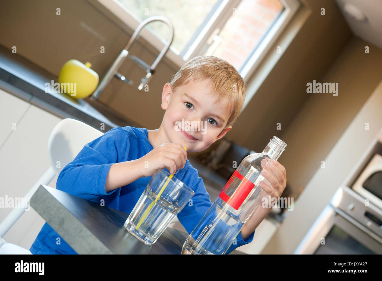5-year old boy drinking water through a straw - Stock Image