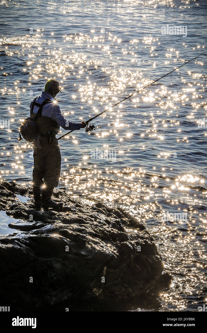 A man heads out fishing early early in the morning while the tide is high,and the sun reflects off the small waves Stock Photo