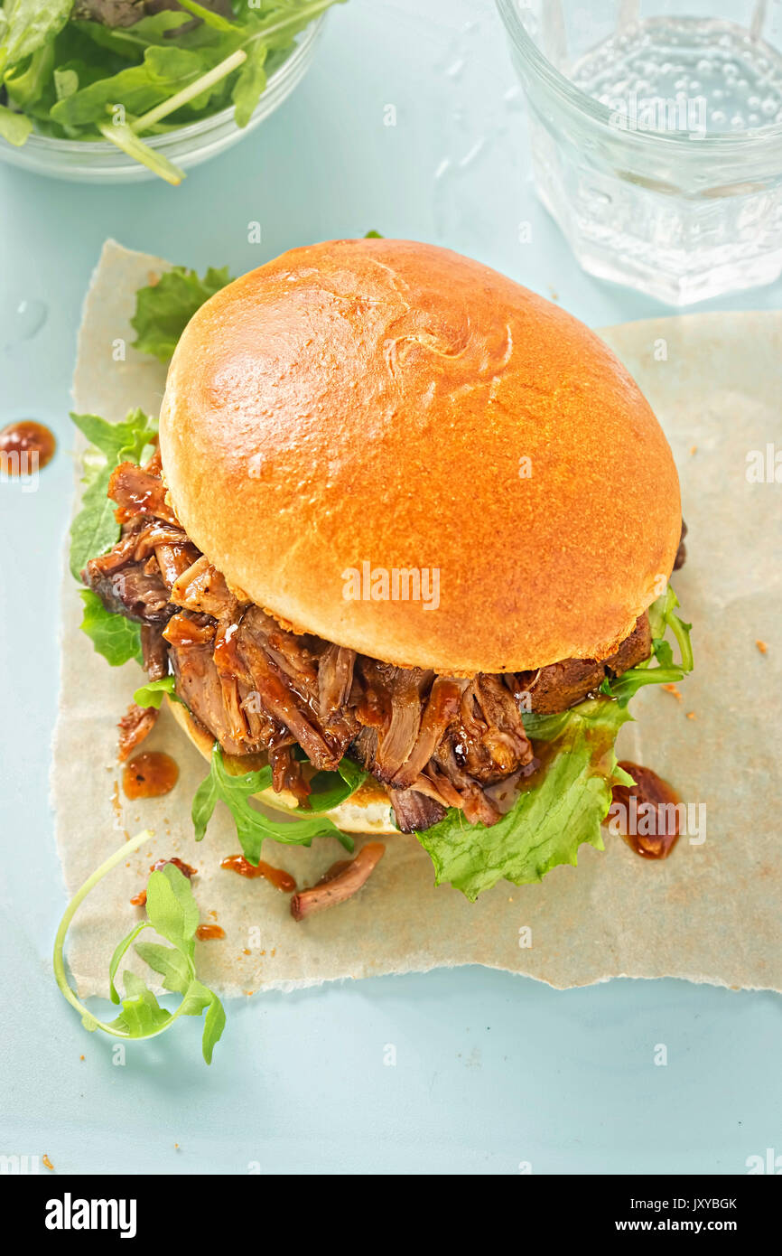 Pulled pork sweet bun with mixed lettuce leaves - Stock Image