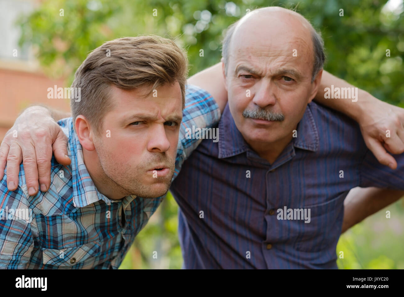 Portrait of doubting men. Dad and son look forward and frown - Stock Image