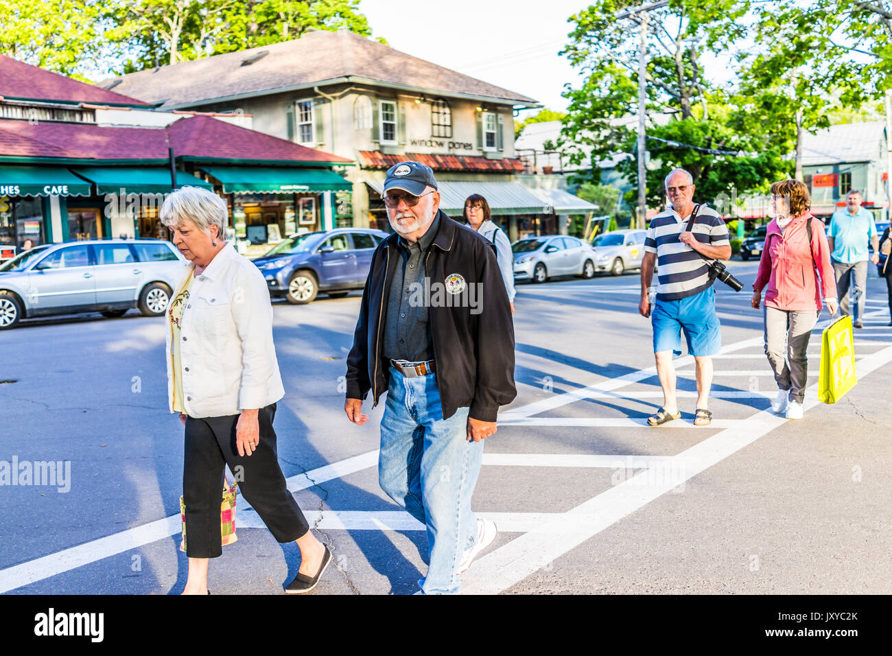 Bar Harbor, USA - June 8, 2017: Happy people crossing sidewalk street in downtown village in summer on main road - Stock Image