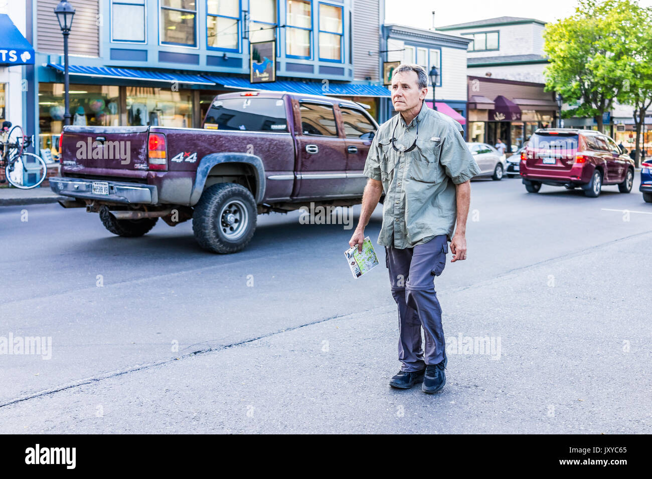 Bar Harbor, USA - June 8, 2017: Lost tourist man holding map crossing sidewalk street in downtown village in summer on main road - Stock Image