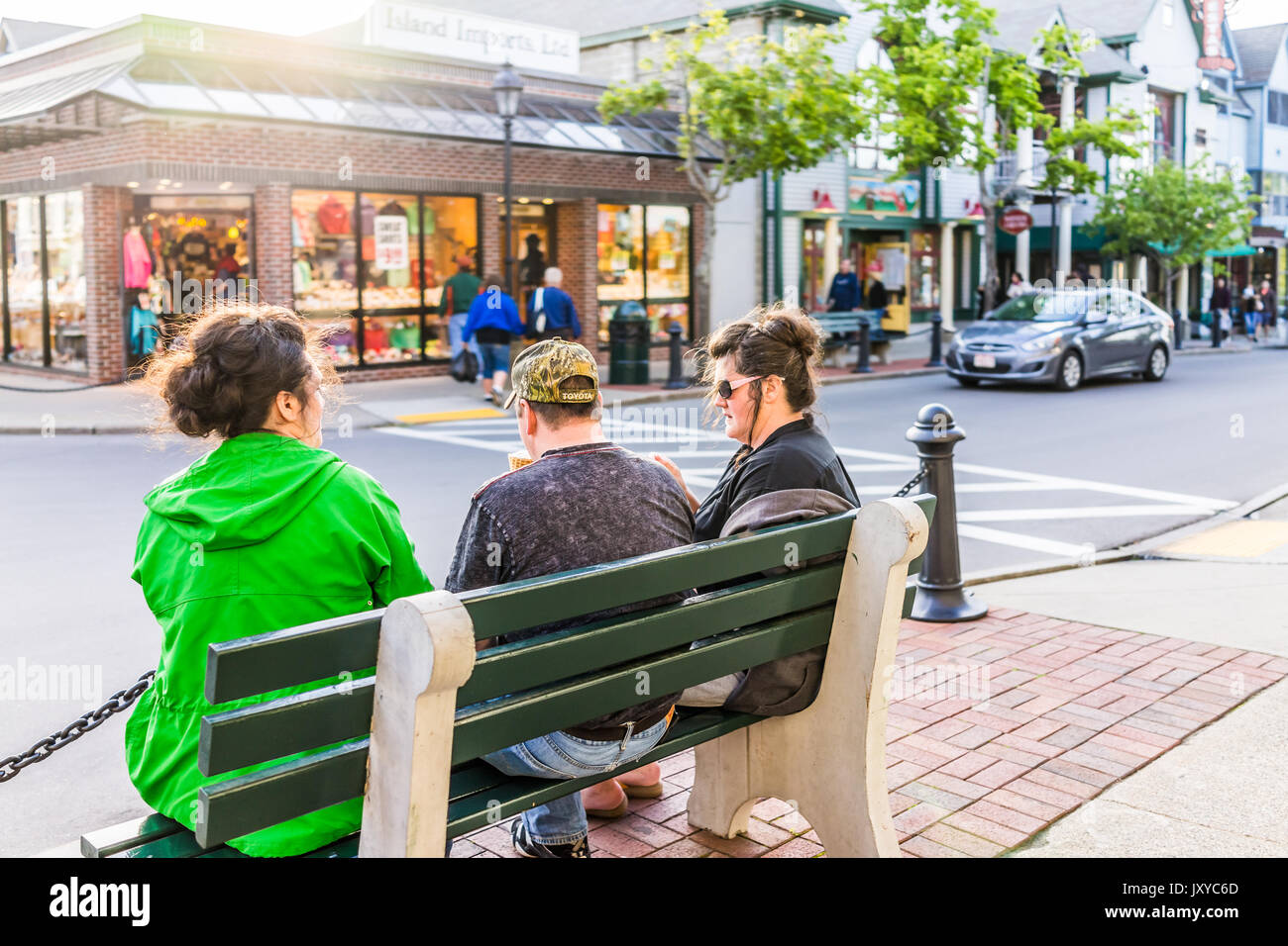 Bar Harbor, USA - June 8, 2017: People on benches in Maine downtown village in summer evening eating ice cream - Stock Image