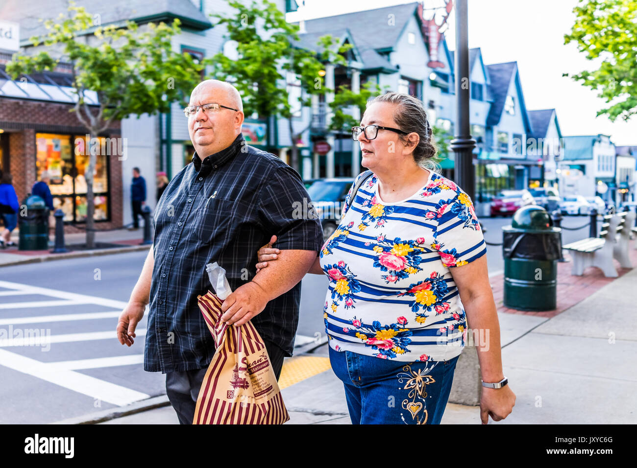 Bar Harbor, USA - June 8, 2017: Couple crossing sidewalk street in downtown village in summer on main road carrying food - Stock Image