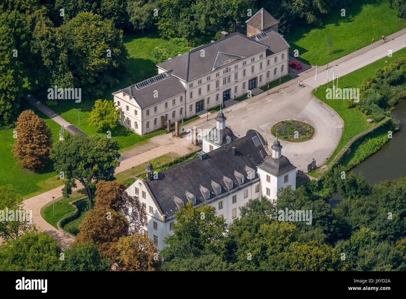 Schloss Borbeck, baroque moated castle, main house and an elongated farm buildings, curly gable, castle park is designed as an English landscape garde - Stock Image