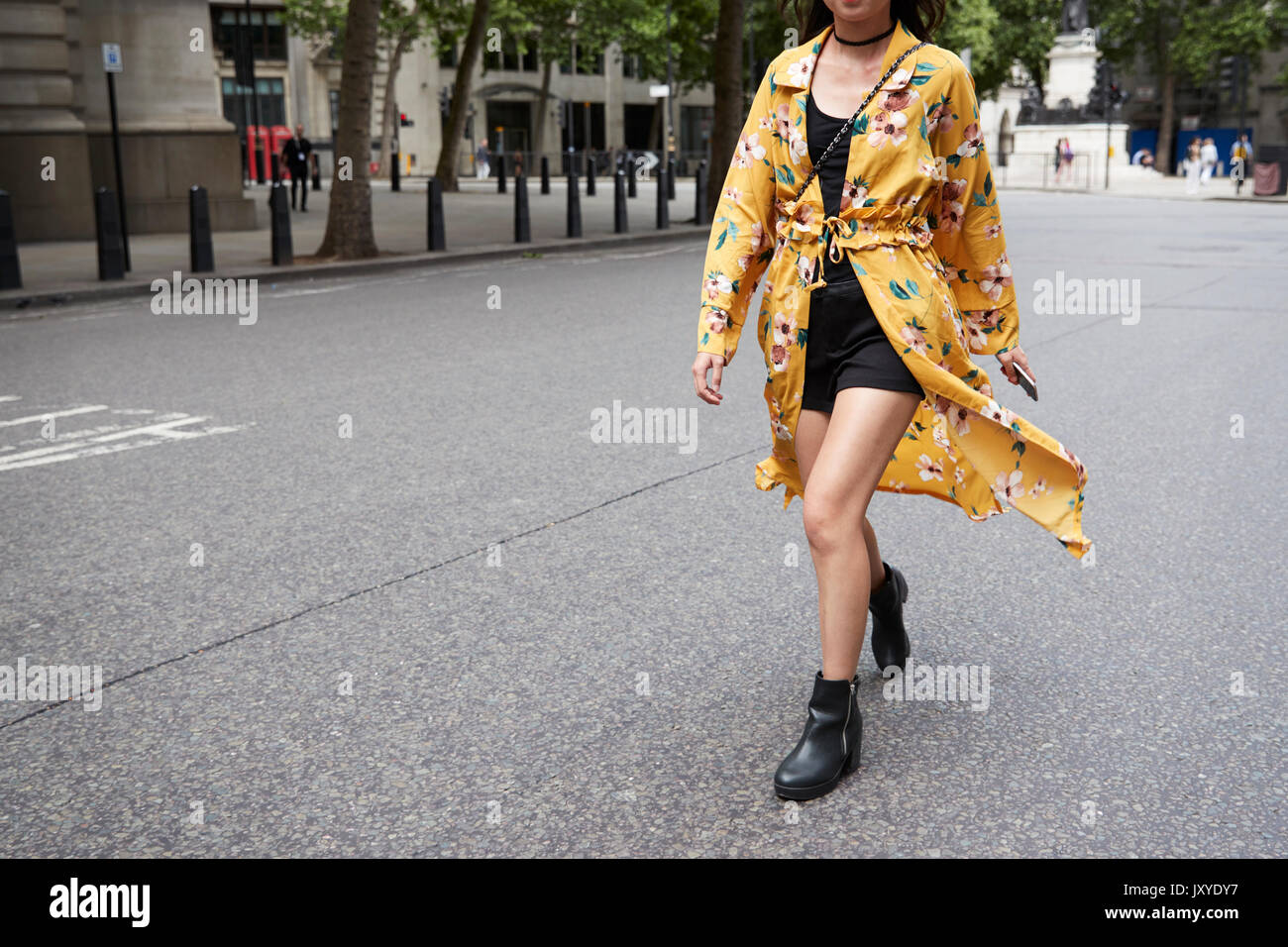 Woman in minidress and floral gown in street, horizontal - Stock Image