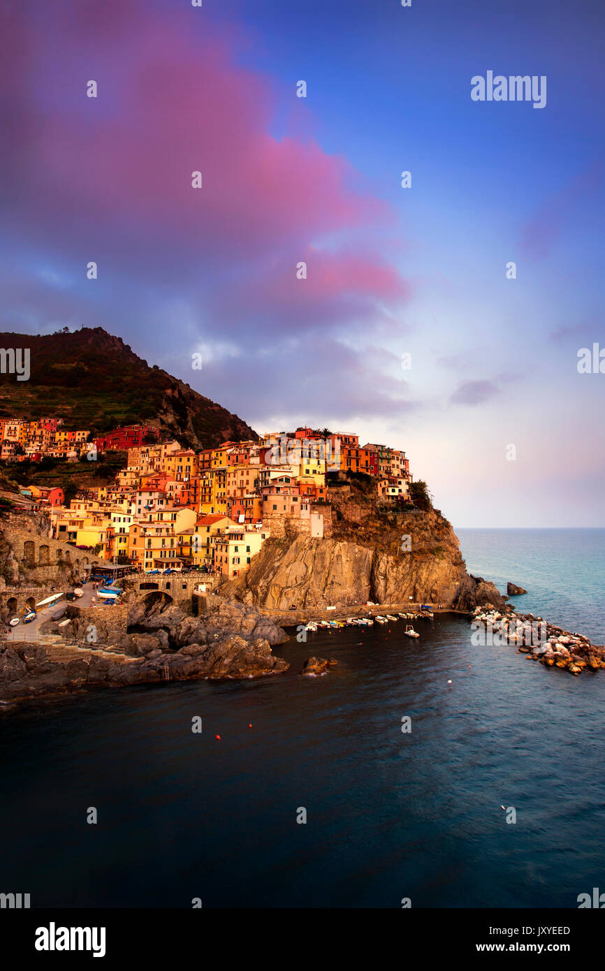 Manarola at sunset.  One of the five towns of the Cinque Terre, the cliff town of Manarola is perched along the Stock Photo