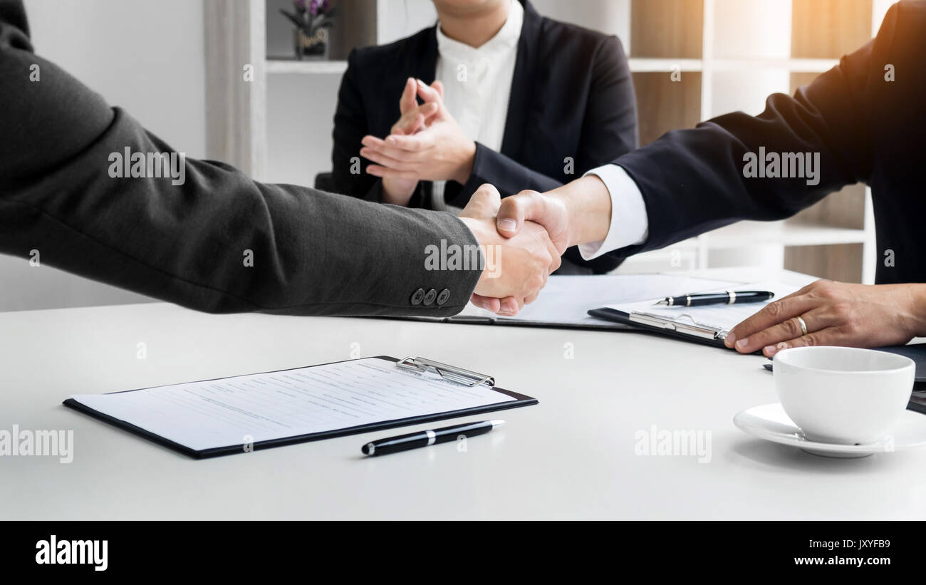 successful business team shaking hands with eachother in the office, job interview concept. - Stock Image