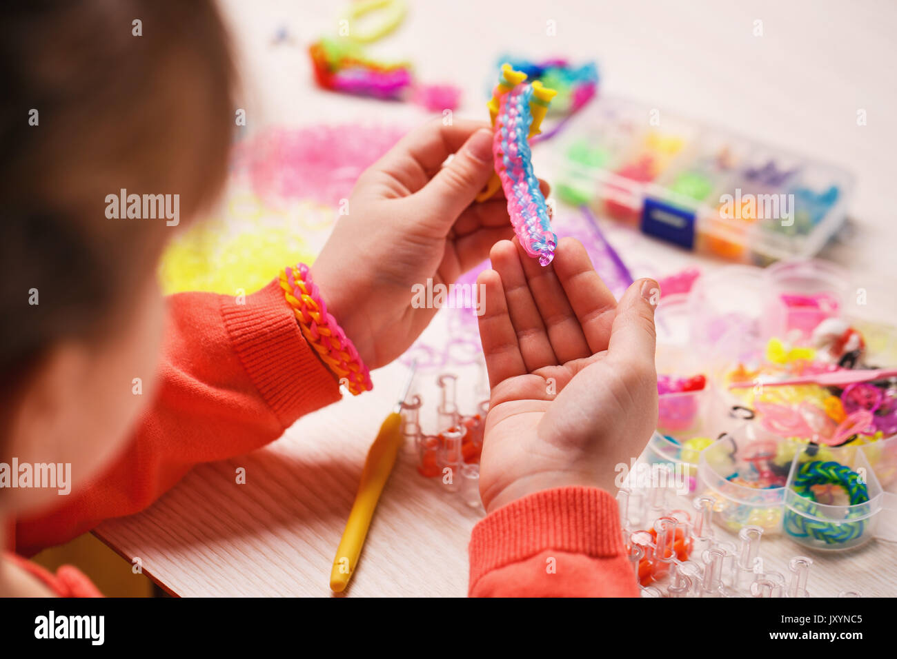 extracurricular activities, group, education and handwork concept - colored rubber bands for weaving accessories in the hands of a girl on a wooden ba - Stock Image