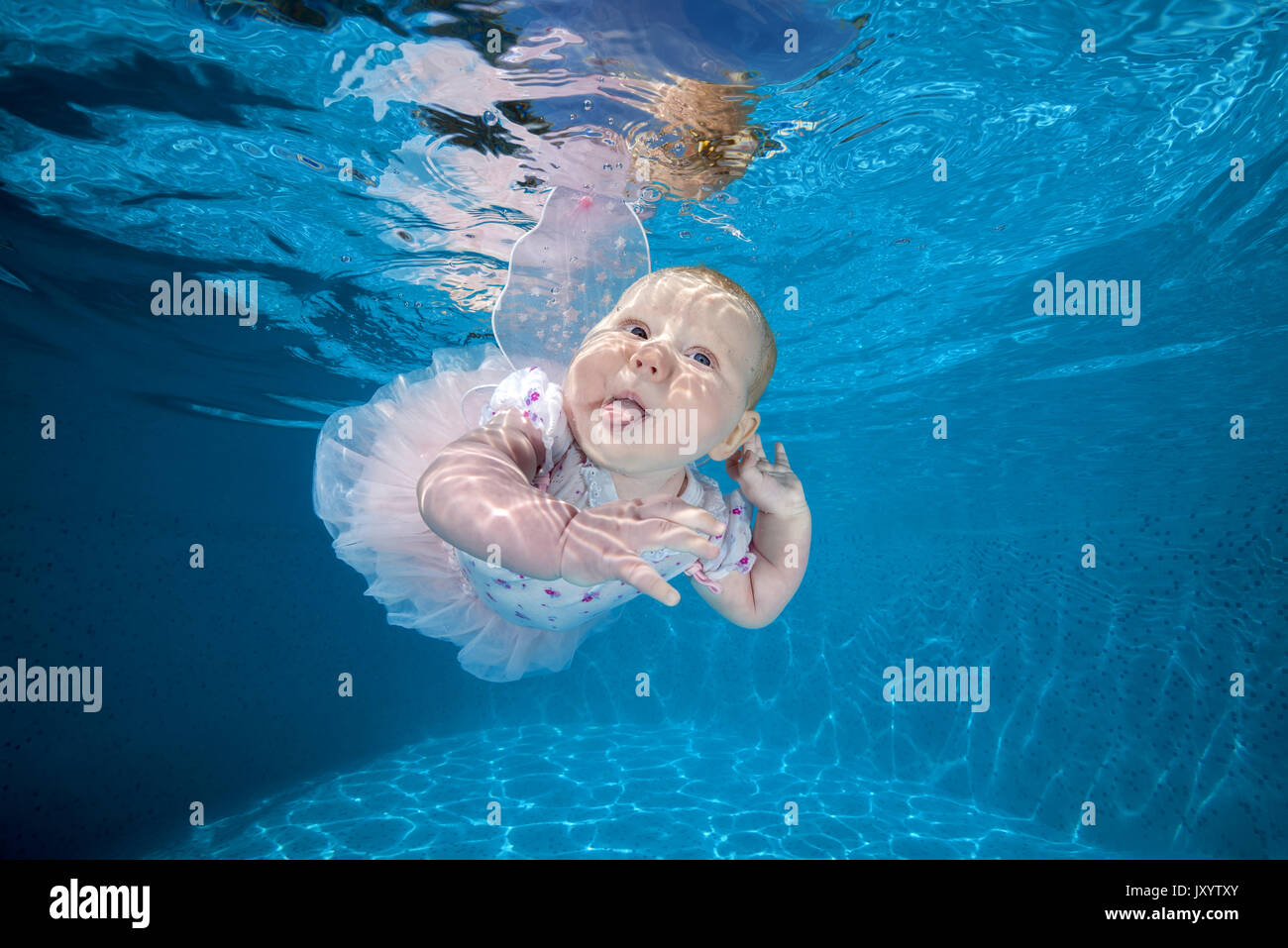 Little girl in fairy dress under water in the pool 2. AMUSING shots show the exhilarated and confused faces water babies can pull when dunked into swi - Stock Image