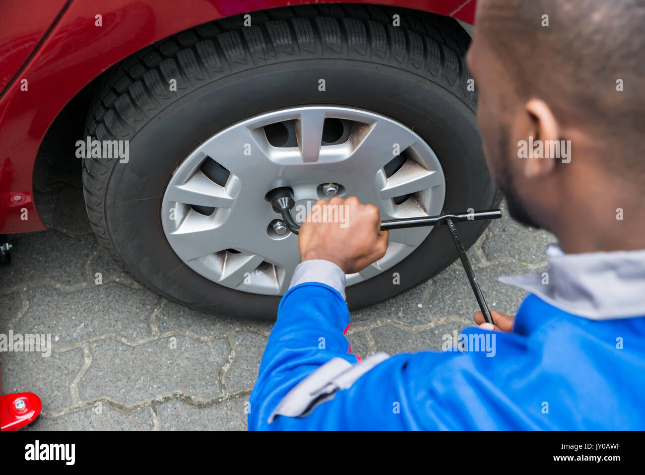 Young African Mechanic Changing Tire Of A Red Car With Wrench - Stock Image