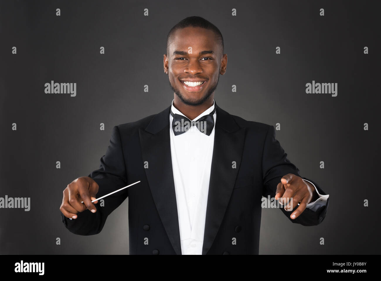Portrait Of Happy Music Conductor With Baton Against Black Background - Stock Image