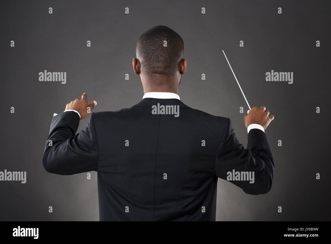 Young African Conductor Directing With His Baton Against Black Background - Stock Image