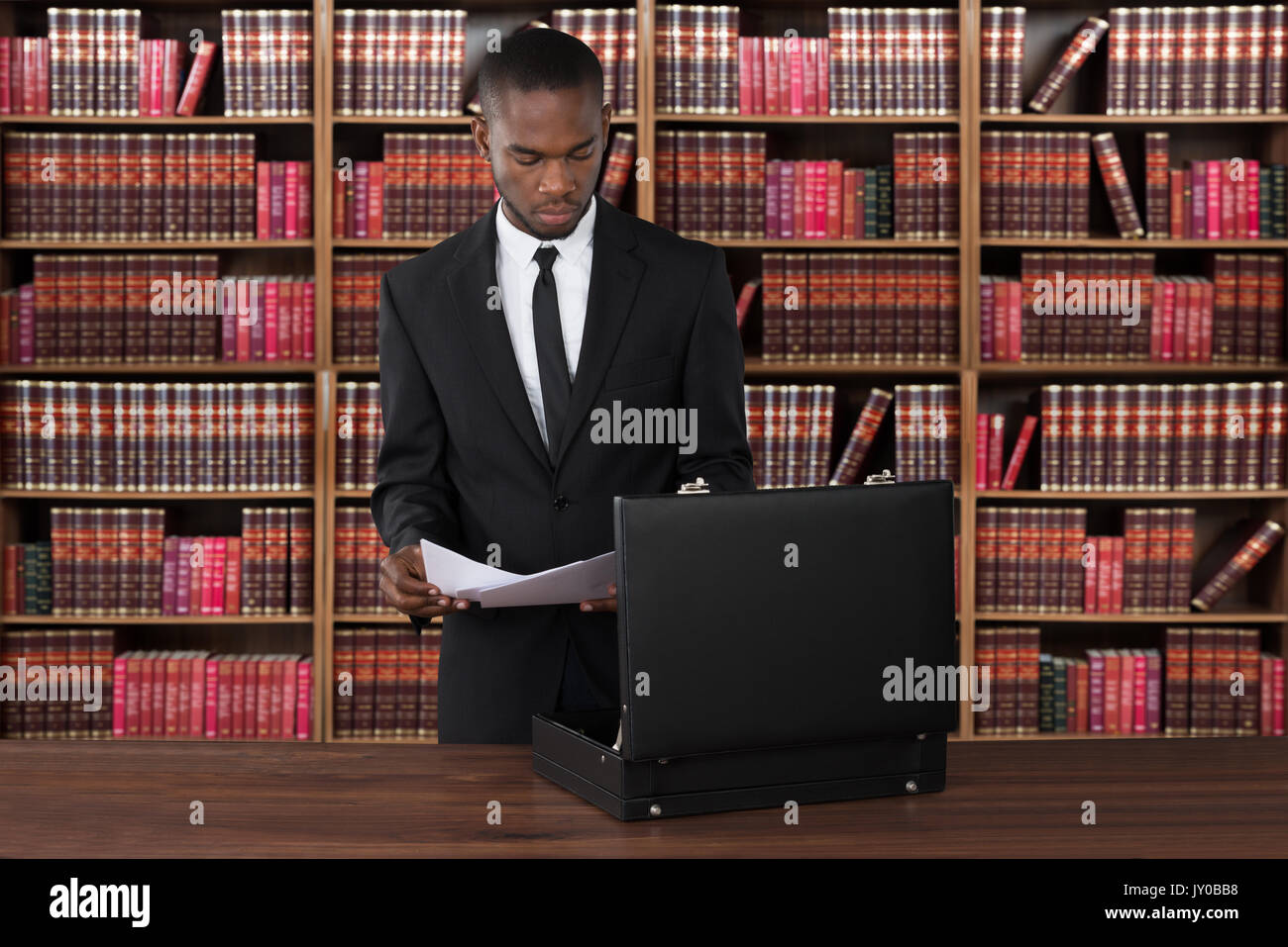 Male Lawyer With Papers And Briefcase At Desk In Office - Stock Image