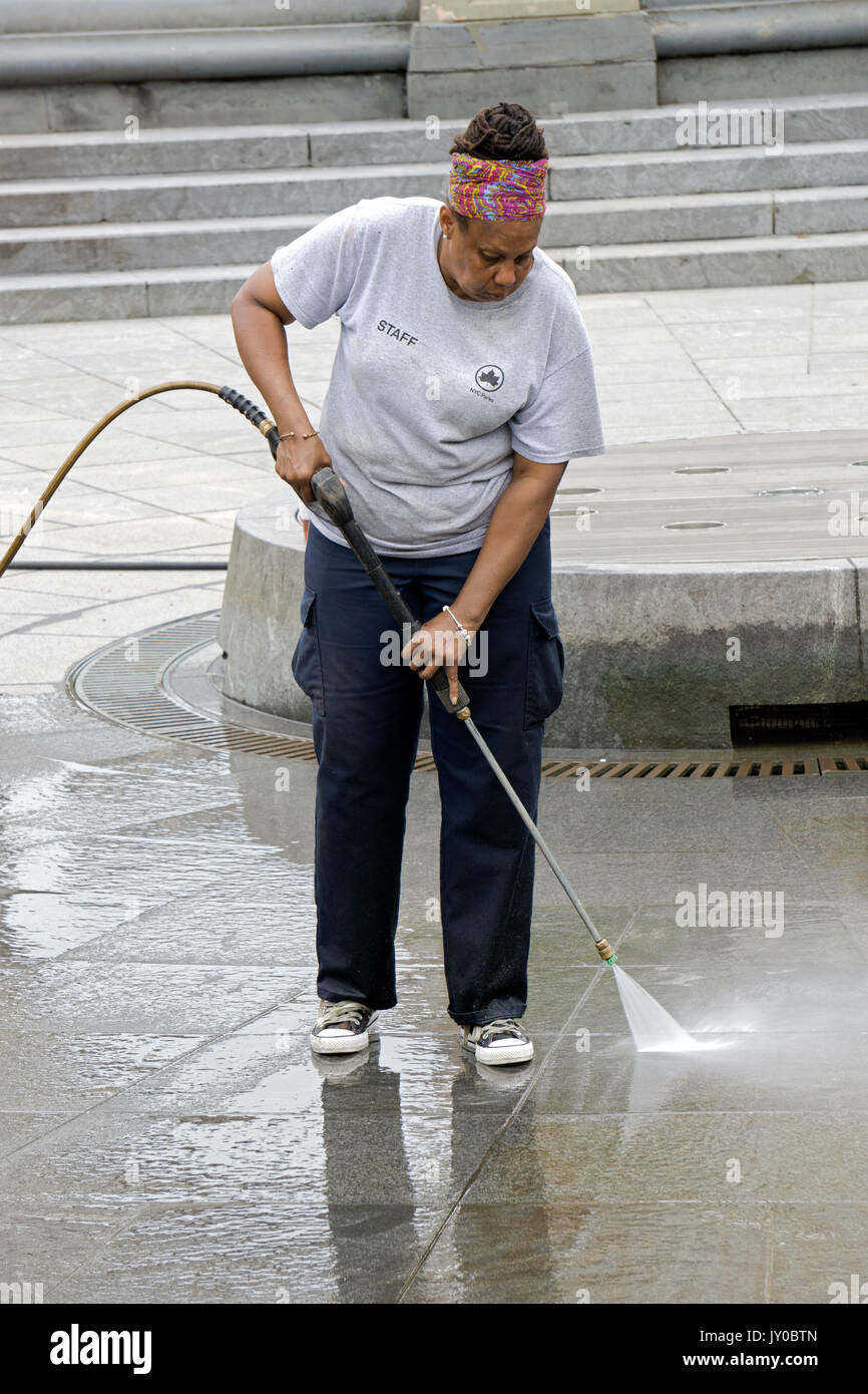 A New York City Parks Dept. worker power washing the fountain area in Washington Square Park in Greenbwich Village, New York City. - Stock Image
