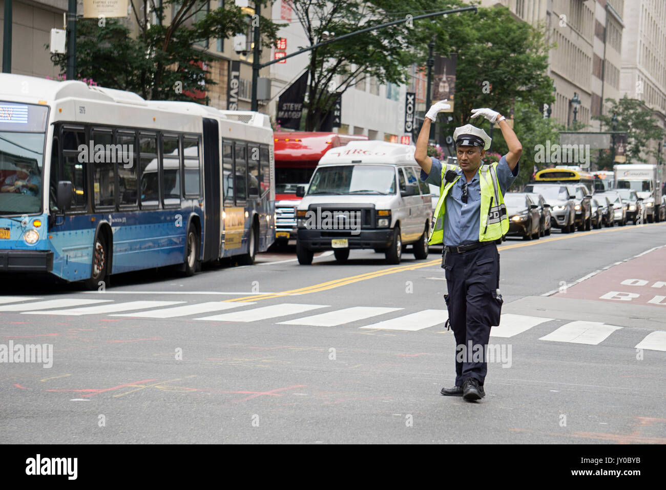 A Bangladeshi police officer directing traffic on Broadway and 34th Street, Herlad Square, in Manhattan, New York City. - Stock Image