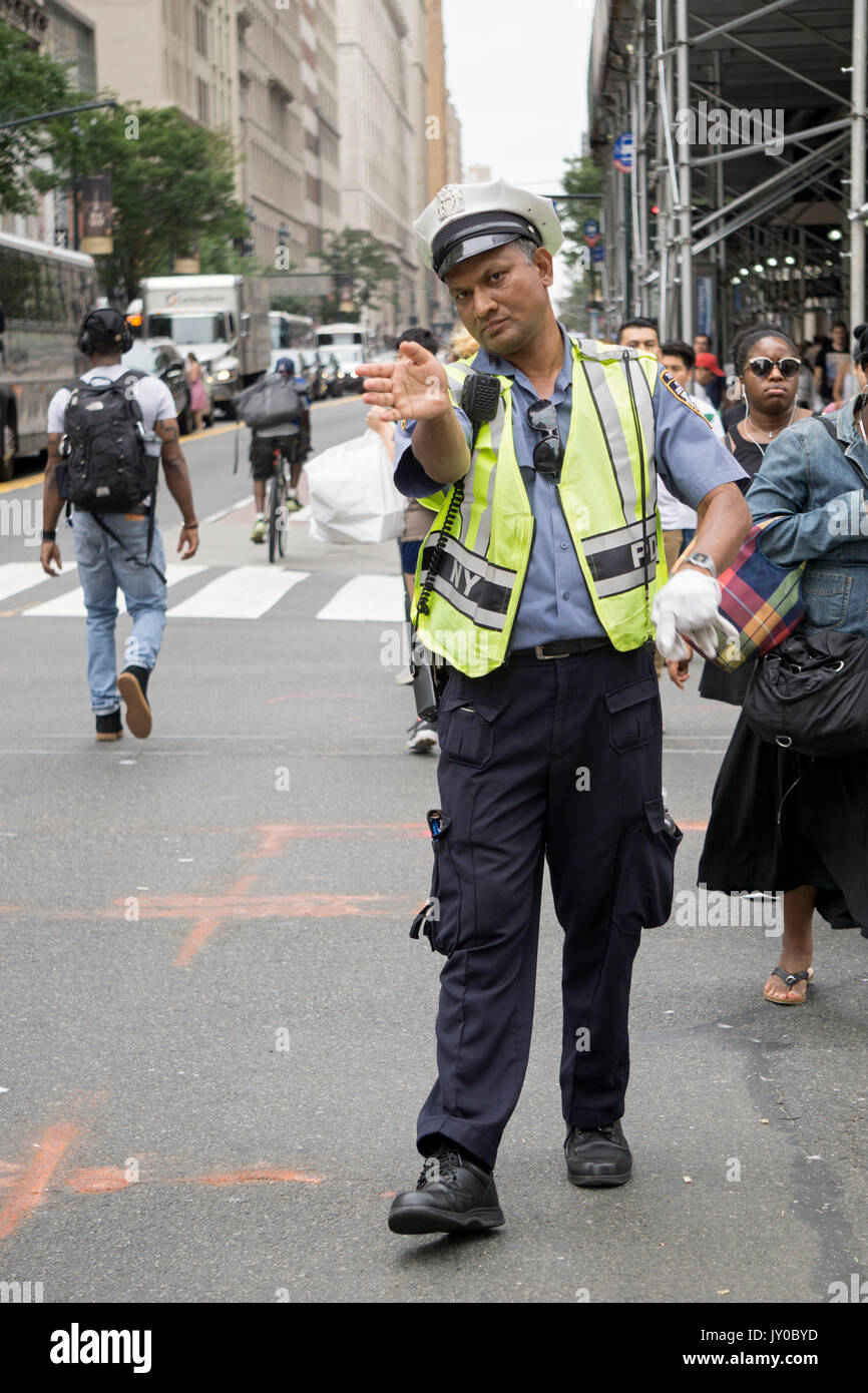 A Bangladeshi police officer directing pedestrian traffic on Broadway and 34th Street, Herlad Square, in Manhattan, New York City. - Stock Image