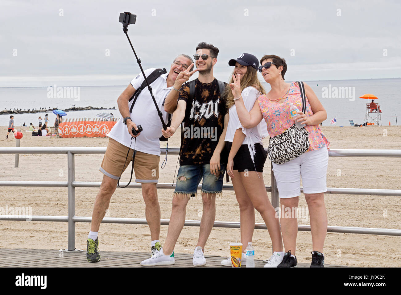A tourist family visiting Coney Island in Brooklyn take a selfie on the boardwalk facing the Atlantic Ocean. - Stock Image
