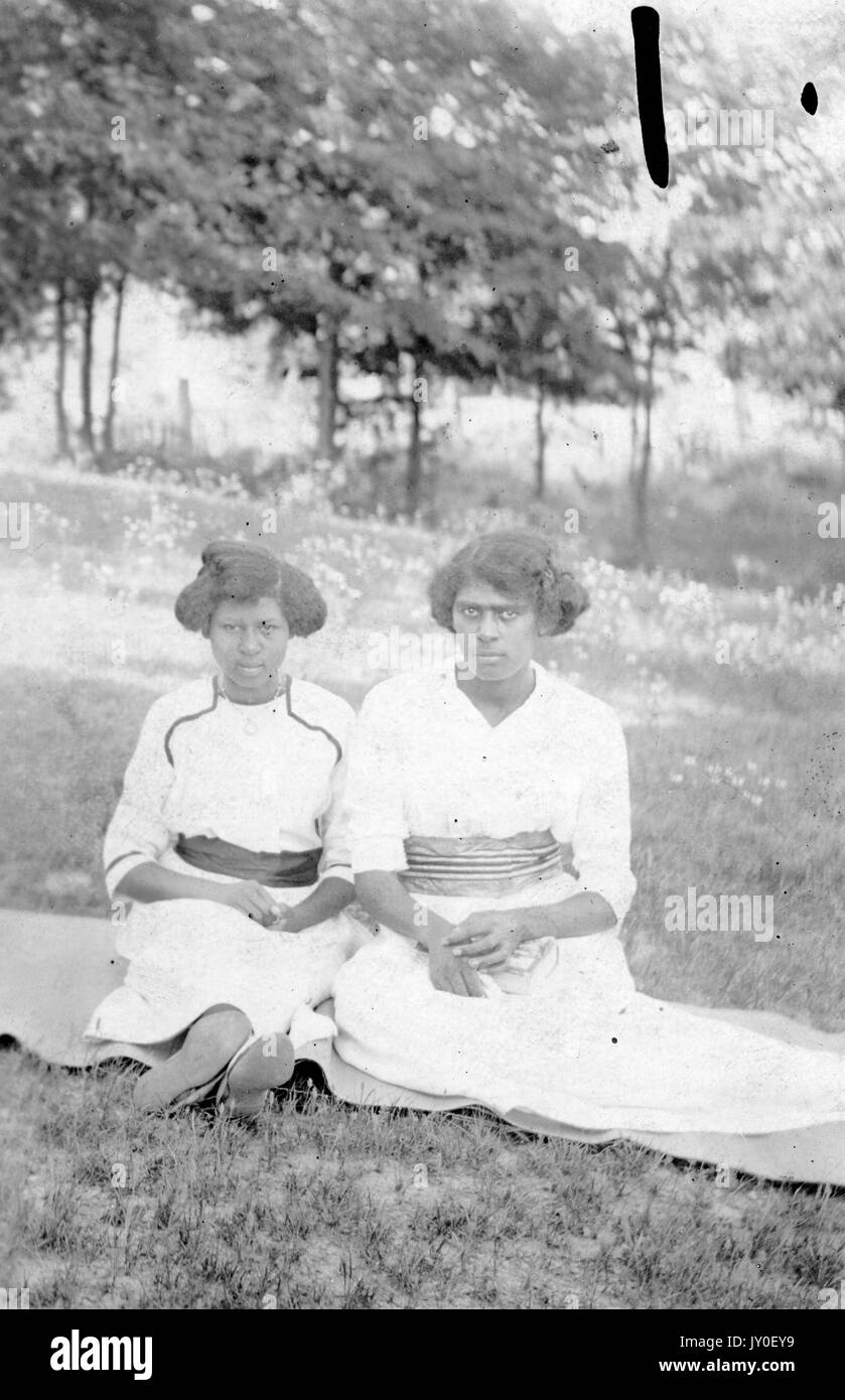 854e75eecdc Full length seated portrait of two young African American women with  serious expressions outside in a field