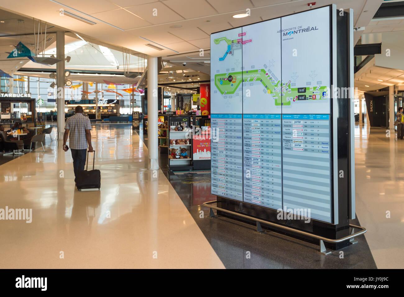Departure hall and display board Inside Montreal Pierre Elliott Trudeau International Airport - Stock Image