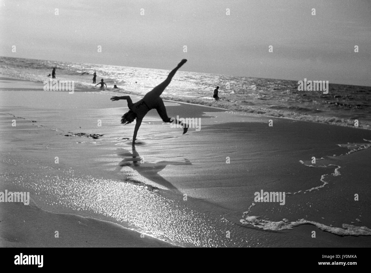 Woman doing cartwheel at the beach.Stock Photo