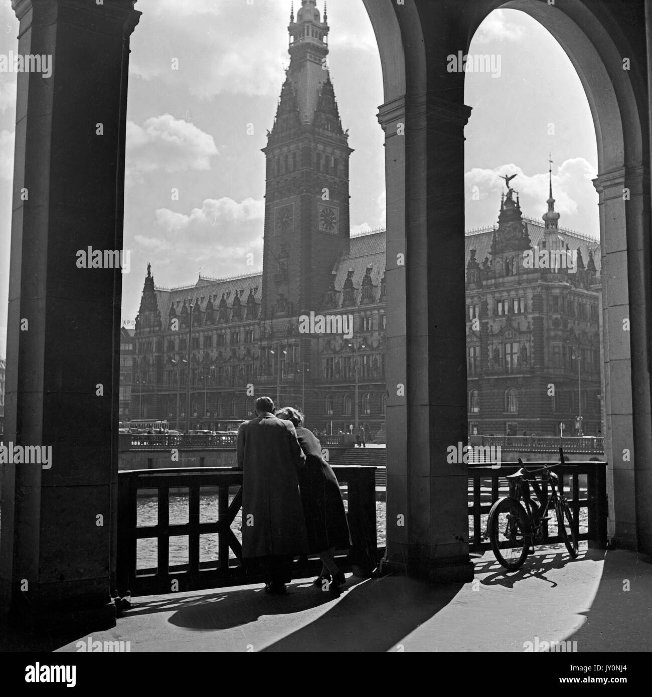 Woman and man standing under arch by water in city. - Stock Image