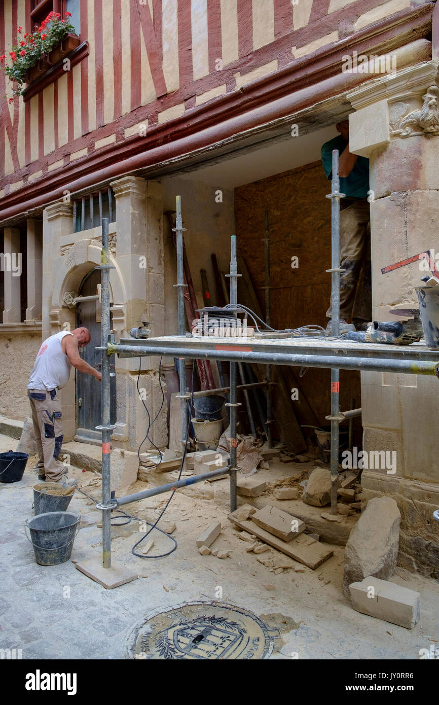 man, work, working, labor, labour, laboring, labouring, repair, renovation, repairing, renovating, medieval, building, architecture, old, house, europ - Stock Image