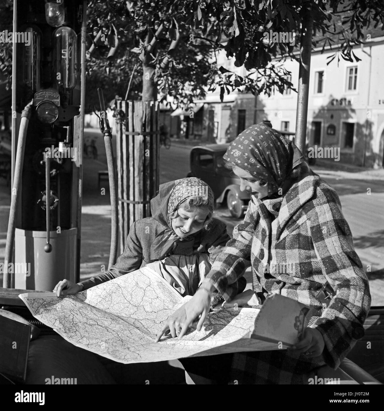 Young women reading map at gas station. - Stock Image