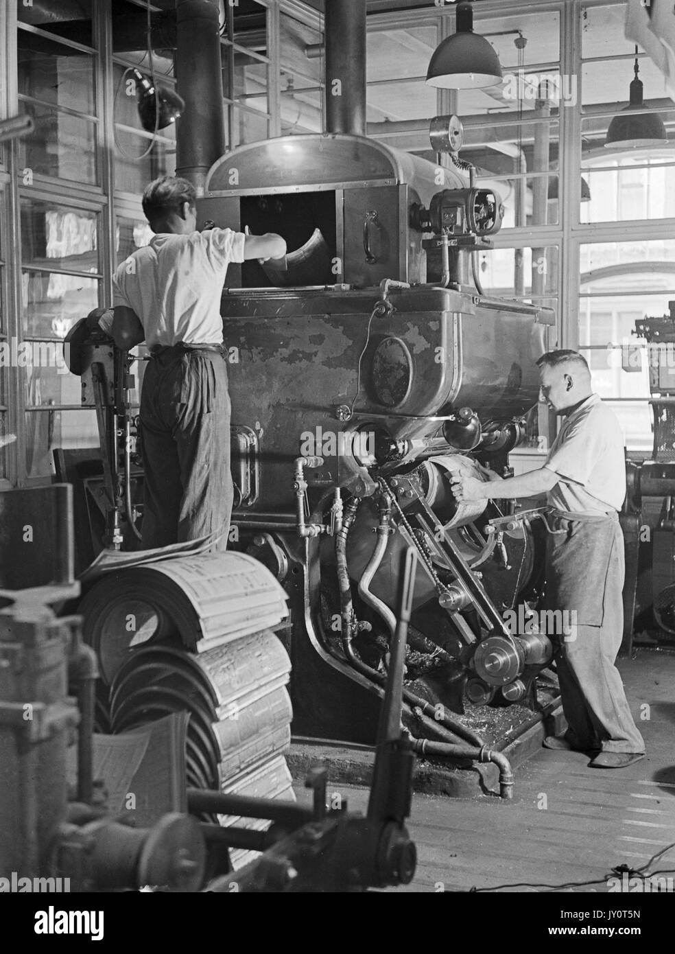 Young Men Working With Old Fashioned Printing Press