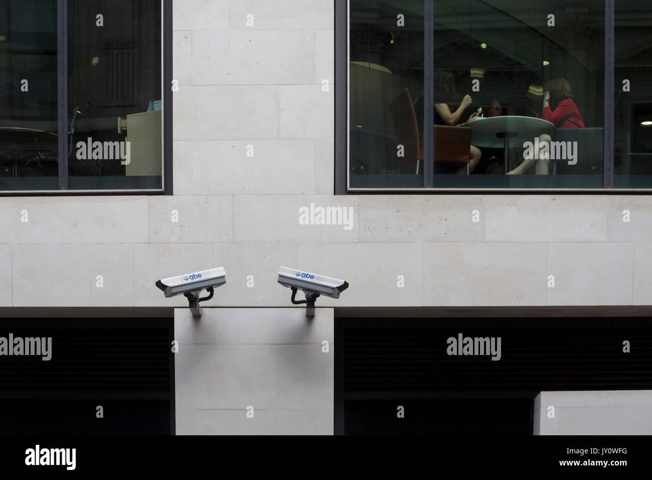 Londoners walk beneath two CCTV cameras in the City of London, one of the most-watched  on 11th August, 2017, in Stock Photo